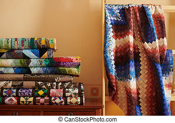 Stack of quilts and quilt made in the bargello style on yellow wall background