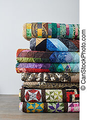 Stack of quilts on white wall background