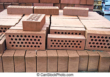 Stack of red clay bricks with holes