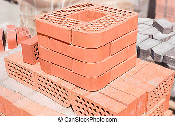 Stack of red decorative face bricks against of another bricks