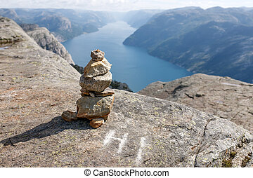 Stack of rocks with mountain and fjord view, on Pulpit Rock...
