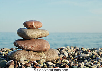 Stack of round smooth stones on a seashore over sea...