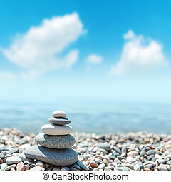stack of rounded stones zen-like and blue sky with clouds