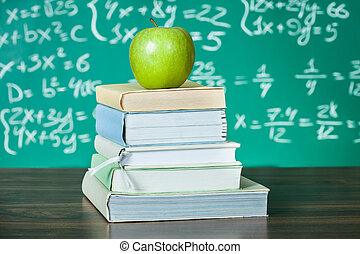 Stack of school textbooks and apple in front of blackboard
