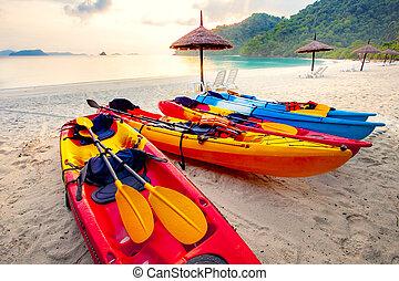 stack of sea kayak on beautiful sand beach against morning usn rising