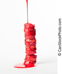 Stack of sliced moisturizing lipsticks with red paint, pouring on them