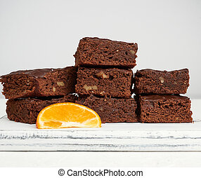stack of square baked slices of brownie chocolate cake with walnuts on a white wooden board