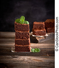 stack of square pieces of baked brownie pie on a wooden board