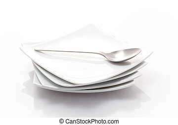 stack of square plates with a spoon isolated on a white background