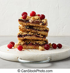 stack of square slices of baked crumble pie with blue plum on a white wooden board