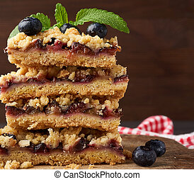 stack of square slices of baked crumble pie with blue plum on a wooden board