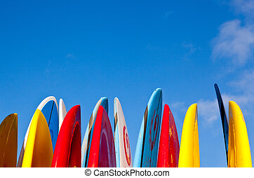 Set of different color surf boards in a stack by ocean