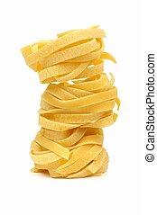 Stack of tagliatelle pasta nests over white