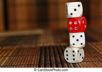 Stack of three white plastic dices and one red dice on brown wooden board background. Six sides cube with black dots. Number 3, 4, 5, 6