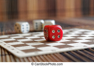 Stack of three white plastic dices and one red dice on brown wooden board background. Six sides cube with black dots. Number 4
