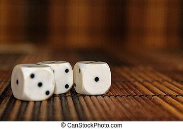 Stack of three white plastic dices on brown wooden board background. Six sides cube with black dots. Number 1, 3