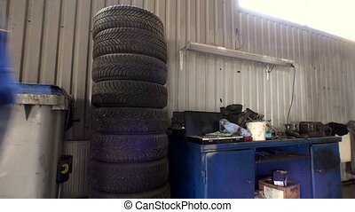 Stack of tires and mechanic take one. Seasonal car tire change in garage.