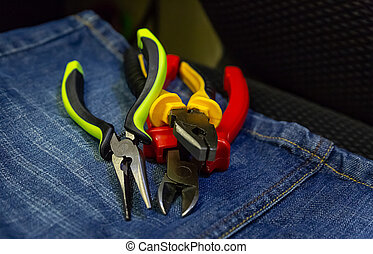 stack of tools hand pliers colorful non-slip handles work with power tools industrial background