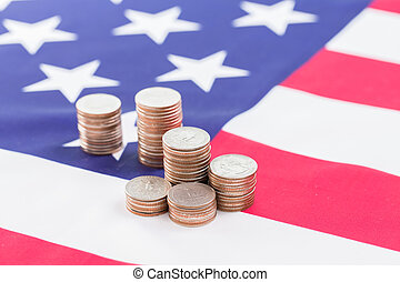 stack of US. dollar coins on American flag