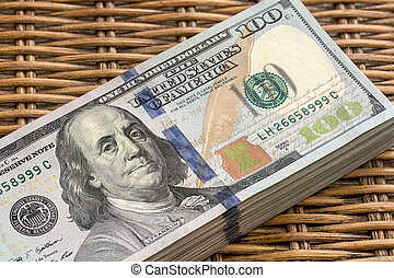 Stack of United States of America USD 100 One Hundred Dollars Federal Reserve Notes Pile on Wicker Background