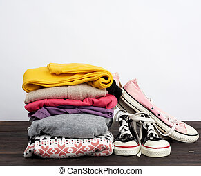 stack of various folded clothes and textile worn cedwas on a wooden table, white background