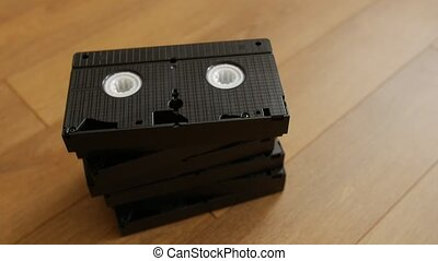 Stack of VHS video tape cassette over wooden background, top view.