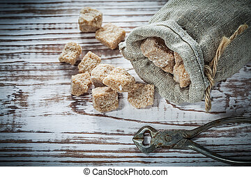 Stack of vintage brown sugar pliers sack on wooden board