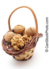 Stack of walnuts in wicker basket on white background