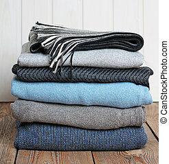 Stack of warm woolen clothing on a wooden table