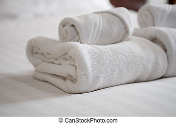 Stack of white bath towels on bed sheet