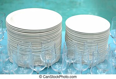 Stack of white plates and glasses