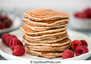 Stack of whole wheat pancakes with raspberries
