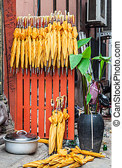 Stack of yellow umbrellas for sale at a stall