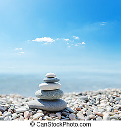 stack of zen stones over sea and clouds background