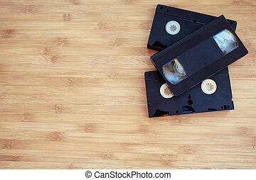 stack old retro video cassette over wooden background.