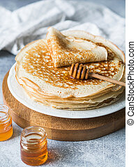 Stack Russian homemade yeast pancakes on white plate, wood honey spoon and honey in jars on grey table. Traditional wheat pancakes for Shrovetide.