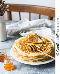 Stack Russian homemade yeast pancakes on white plate, wood honey spoon and honey in jars on table. Traditional wheat pancakes for Shrovetide.