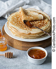 Stack Russian homemade yeast pancakes on white plate, wood honey spoon, honey in jars and apricot jam in bowl on grey table. Traditional wheat pancakes for Shrovetide.