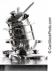 Stack with stainless steel pots and pans on white background