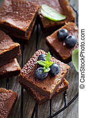 Stacked brownies with a cup of tea near a chalkboard