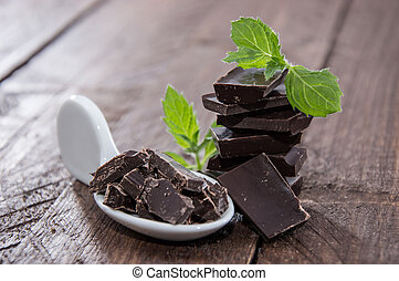 Stacked Chocolate with Mint on wooden background