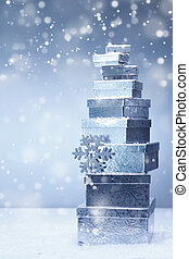 Stacked Christmas gifts in winter snowfall