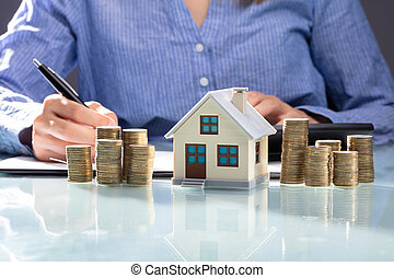 Stacked Coins And House Model On Desk