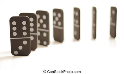 Stacked dominoes tipping over isolated on white - A bunch of...