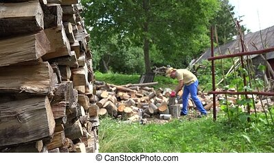 Stacked firewood and blurred farmer man chopping wood in backyard. 4K