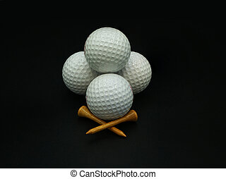 Stacked golf balls and tees on black background
