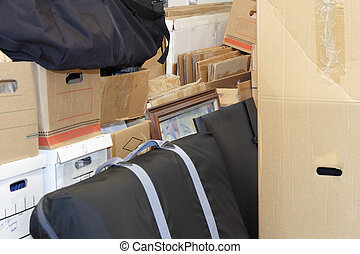 Close up of many packed and empty moving boxes, and cases of various sizes stocked on top of and in front of one another in preparation of a move.
