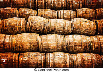Stacked pile of old vintage whisky and wine wooden barrels...