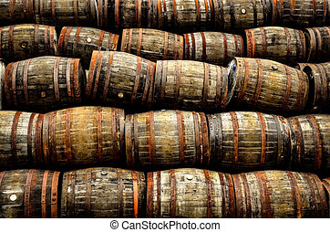 Stacked pile of old whisky and wine wooden barrels and casks