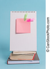 Stacked piled books standing spiral notebook sticky note arrow banners lying peaceful cool pastel background. Empty text future important events